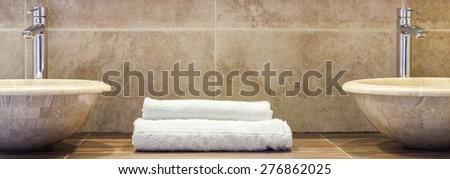 White clean folded towels on marble shelf in bathroom