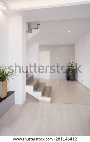 White clean hallway with wooden stairs on the first floor #281146412