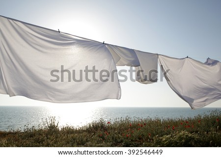 White clean sheets outdoors. Drying on a rope on background of beautiful scenery in the sun