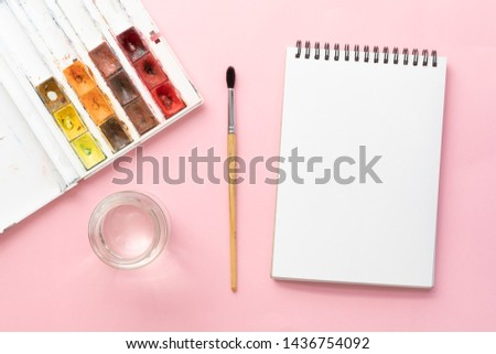 White clean sketchbook on black spring, squirrel brush, jar of water and watercolor paints on pink paper background with copy space, top view. Artist workspace concept