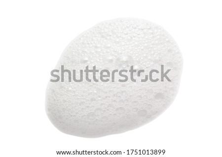 White cleanser foam bubbles drop isolated on white. Soap, shower gel, shampoo foam texture closeup