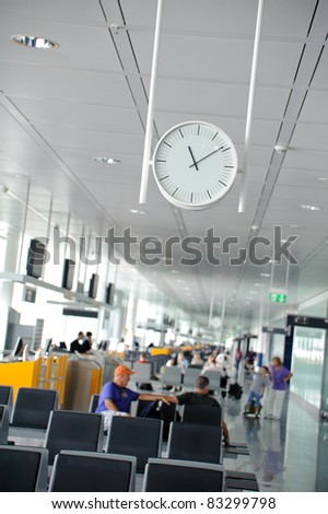 White clock in a waiting lounge in an airport terminal with people sitting in the background