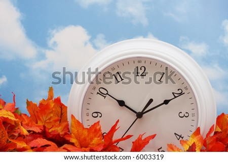 white clock on fall leaves, sky background