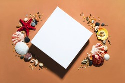 White close square gift box mockup template top view with copy space. Layout package clipart. Tropical seashells, sand and stones decor. Summer modern concept flat lay on brown orange background