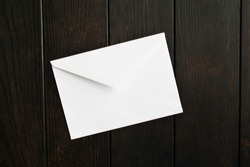 White closed envelope over brown wooden table. Empty letter. Paper mail for note. Mockup. Top view. FLat lay