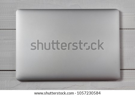 White closed laptop on wooden table background. Stiduo shot. #1057230584