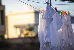 White clothes hanging in the sun to dry, attached to the rope by colored paper clips, blurred background
