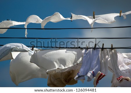 White clothes hanging on the line seen against a blue clear sky