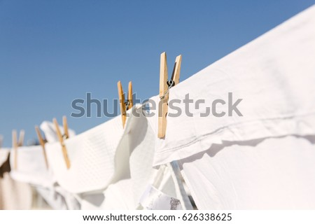 Shutterstock White clothes hung out to dry on a washing line in the bright warm sun. Background is a clear blue sky.