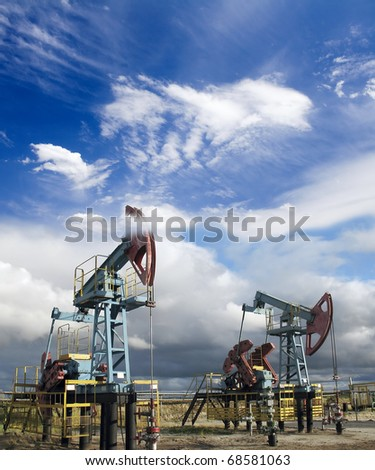 White clouds above oil pumps. Industrial scene