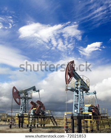 White clouds and oil pumps. Industrial scene