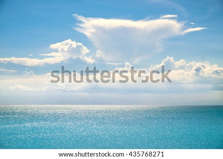 White clouds and sun beams on a blue sky over calm sea with sunlight reflection, Bali, Indonesia. Sunny sky with fantastic clouds and blue sea. Calm sunny sea and sky. Bali sea. Sea and sky. Calm sea.