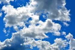 White clouds float across a bright blue sky on a Sunny day. Beautiful atmospheric phenomenon. Natural horizontal background.