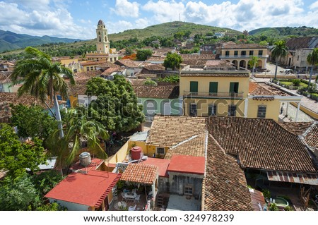 White clouds float in blue sky above the terra cotta rooftops of the historic colonial architecture in the UNESCO heritage center of Trinidad, Cuba
