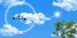 White clouds, flying airplane and round rainbow in the clear sunny sky. The sun shining through the green tree branches. stretch ceiling picture