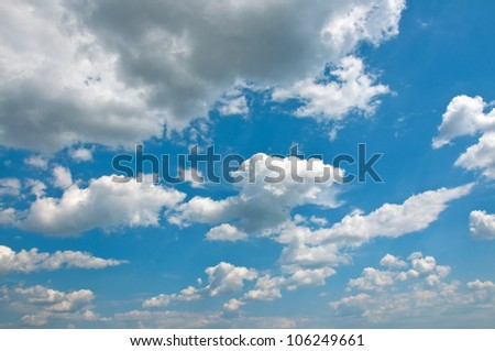 White clouds in blue summer sky. This cloudscape image is suitable as a background for your design.
