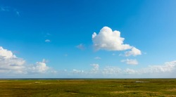 White clouds in the blue sky above the monotonous flat landscape of the North German coast in Friesland