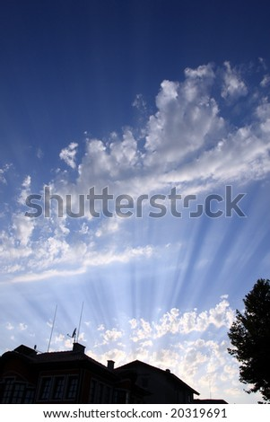 White clouds on blue sky. Rays. Building. Tree.