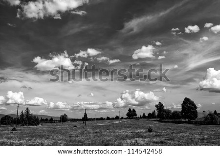 white clouds on the dark sky in  a black and white landscape