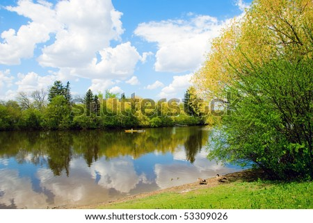 White clouds reflecting in the river water. - stock photo