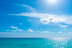 White clouds with blue sky and sun over calm sea  in tropical Maldives island