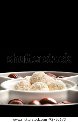 White coconut chocolate balls on plate, isolated on black background