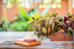 White coffee cup and red book on old wooden table and garden background