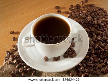 White coffee cup and saucer stands on a wooden table with a lot of coffee beans, top view