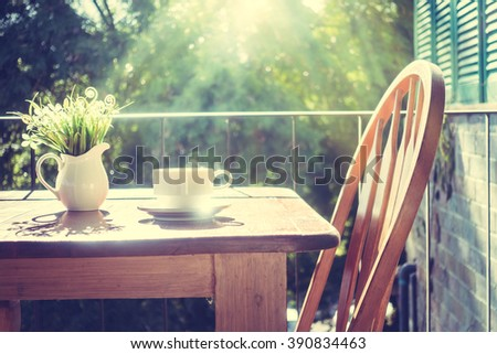 White coffee cup and vase plant on table at patio with outdoor view - Vintage Filter