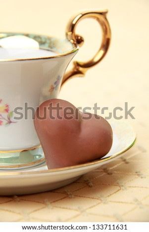 White coffee cup full of coffee beans and chocolate candy on the beige tablecloth on Food and Drink
