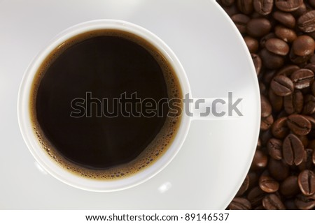 White coffee cup on the background of fresh baked coffee beans.