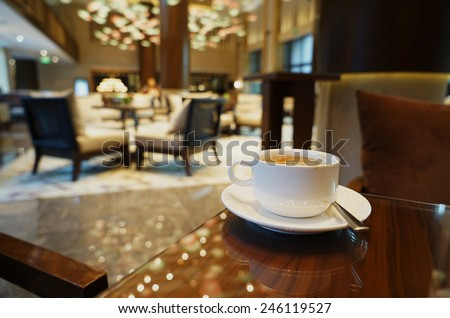 White Coffee cup on the table in lounge bar background. #246119527