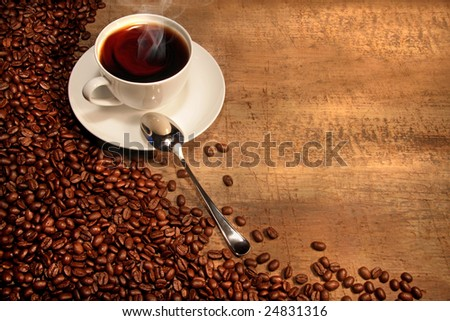 White coffee cup with beans on rustic wooden table