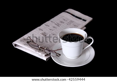 White coffee cup with newspaper and lenses