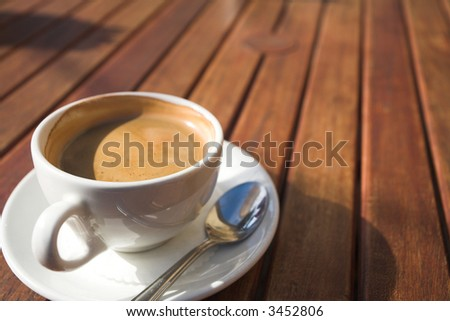 White coffee cup with rich coffee and foam on a brown wooden table – Shallow Depth of Field – focus on rim of cup - stock photo