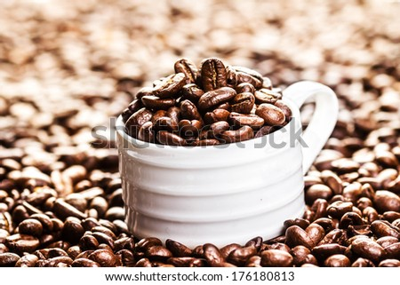 White Coffee Cup with roasted coffee beans on heap of coffee beans background. Coffee background texture with copy space for text, close up.