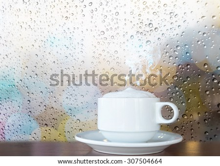 White coffee cup with smoke on the wooden table and water drop grass