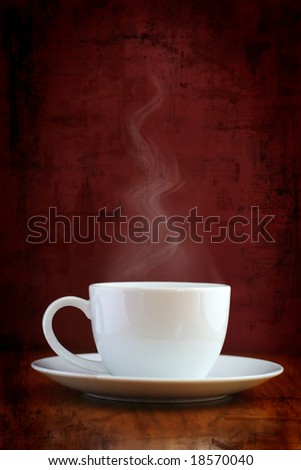 White coffee cup with steaming hot drink on grungy background