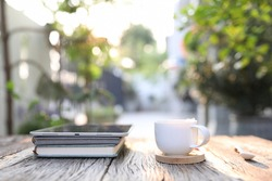 White coffee cup with tablet and notebook at outdoor