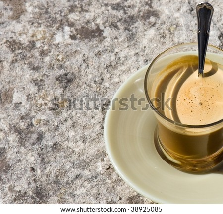 White coffee in glass on stone