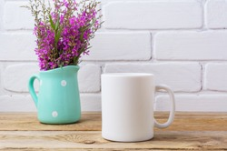 White coffee mug mockup with maroon purple field flowers in polka dot mint green pitcher vase.  Empty mug mock up for design promotion.