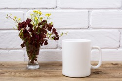 White coffee mug mockup with yellow and maroon wild grass in the simple glass vase.  Empty mug mock up for design promotion.