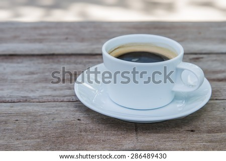 White Coffee Mug shot close to right on a wooden table.