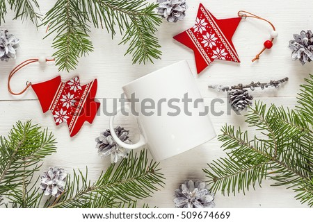 White coffee mug with Christmas decorations and fir branches. Space for text or design. Christmas concept white coffee mug. Top view.