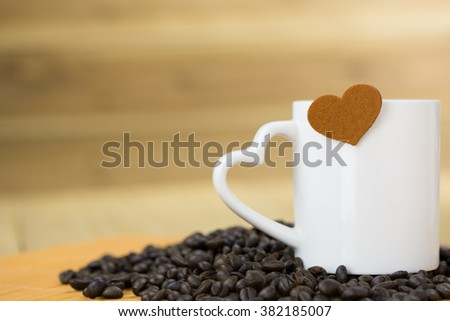 white coffee mug with raw coffee bean and brown heart logo shape over edge with wood background #382185007