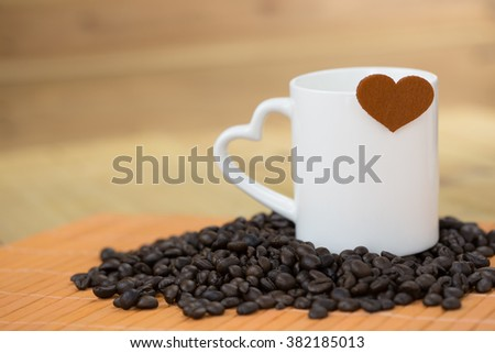 white coffee mug with raw coffee bean and brown heart logo shape over edge with wood background #382185013