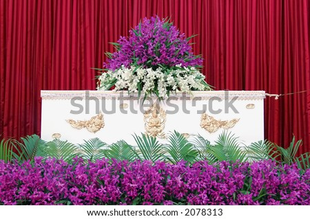White coffin with flowers at a Thai funeral