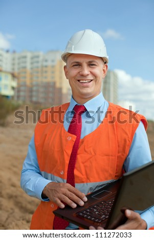 White-collar worker wearing protective helmet works on the building site