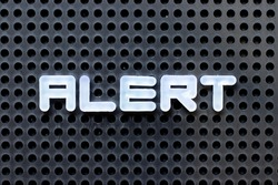 White color alphabet with word alert on black pegboard background