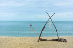 white color dream catcher hanging on woods at the beach with sea background, copy space